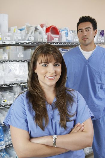 Female and male nurse standing by shelves with medical supply portrait