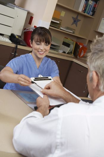 Nurse and senior doctor with paperwork in clinic
