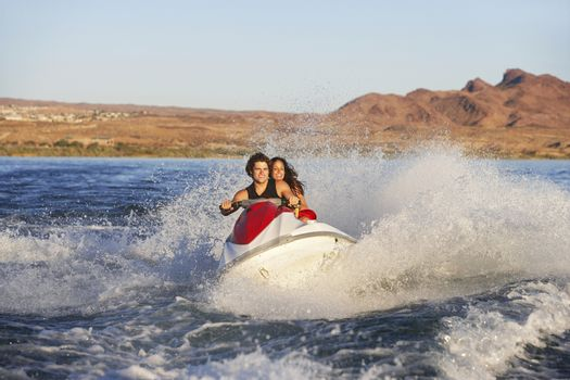 Happy young Caucasian couple riding water scooter on lake