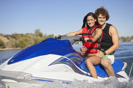 Portrait of a happy Caucasian couple riding water scooter on lake
