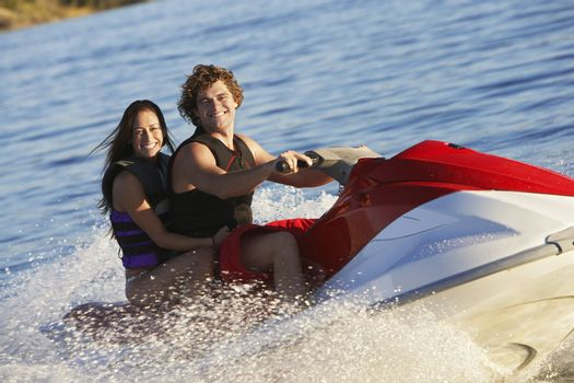 Happy young Caucasian couple riding PWC on lake