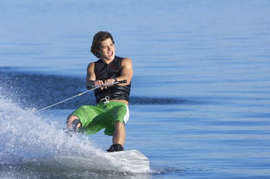 Young Caucasian man wakeboarding on lake