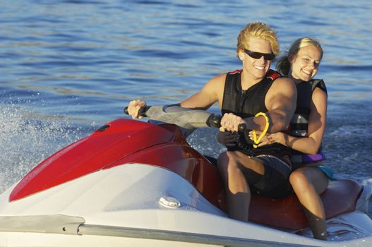 Happy young Caucasian couple riding personal watercraft on lake
