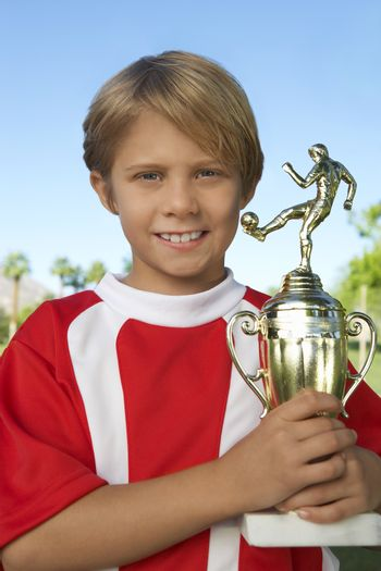 Portrait of young boy holding soccer trophy with pride