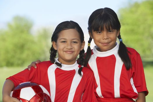 Portrait of two female soccer players with arm around on field