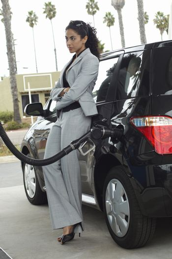 Businesswoman waiting while gasoline refueling her car at fuel station