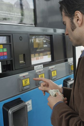 Man pushing buttons on gasoline fuel pump