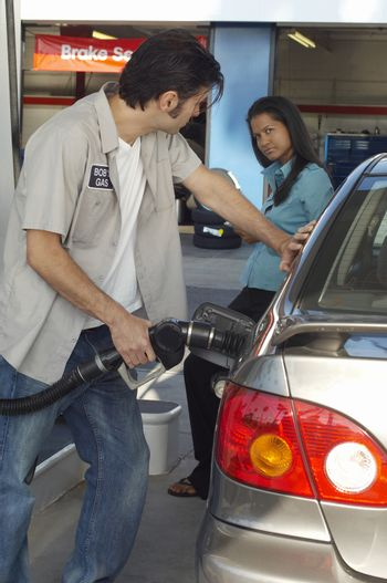 Woman looking at gas station attendant pumping gas into car