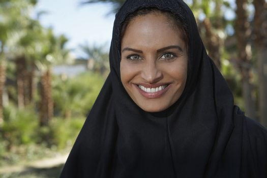 Portrait of a happy Muslim woman in black headscarf