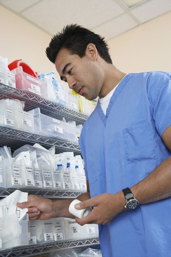 Male nurse standing by shelves with medical supply