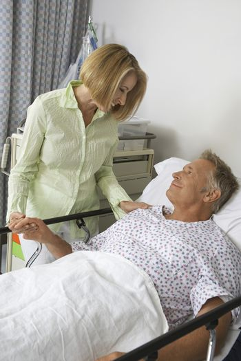 Senior woman visiting male patient in hospital