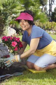 Portrait of a happy woman planting flower plant in garden
