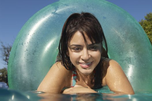 Closeup portrait of a beautiful woman in inflatable ring at swimming pool