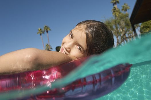 Portrait of a cute girl floating on inflatable ring in swimming pool