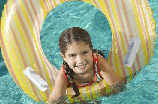 Portrait of a cute elementary girl with inflatable ring in swimming pool