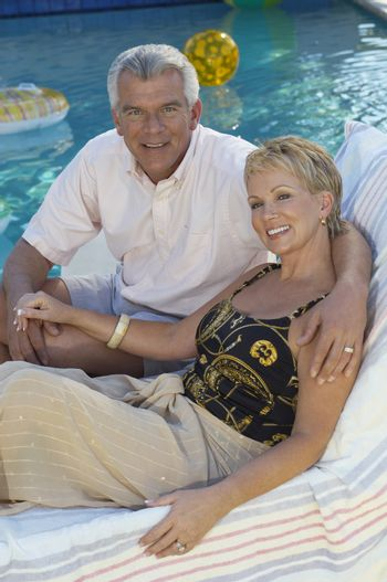 Portrait of a happy couple sitting together on deckchair with arm around
