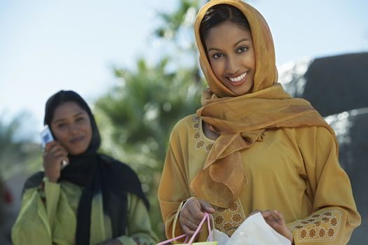 Two muslim woman one with shopping bag