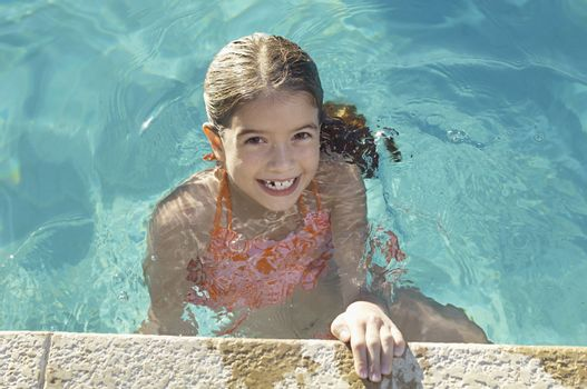 Portrait of a little girl at the edge of the swimming pool