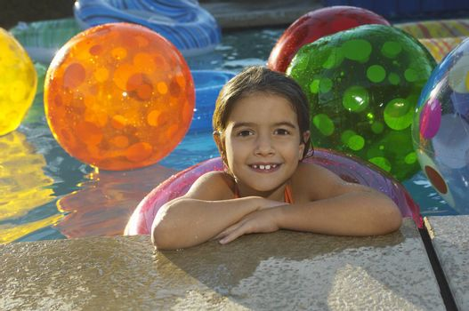 Portrait of a cute little girl with floating ring and beach balls in the swimming pool