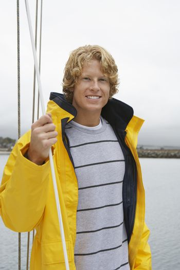 Portrait of a happy Caucasian man holding rope on sailboat