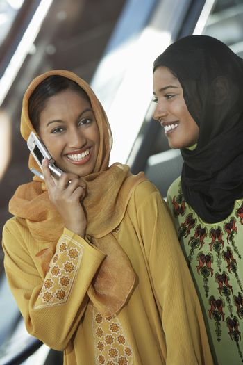 Two muslim woman one talking on mobile