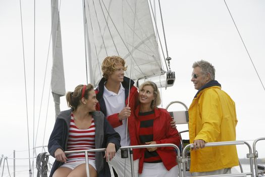 Happy Caucasian family of four on sailboat in sea