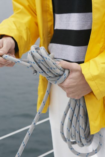 Midsection closeup of a man tying rope on sailboat