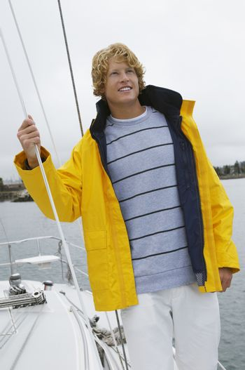 Young Caucasian man standing on sailboat looking away
