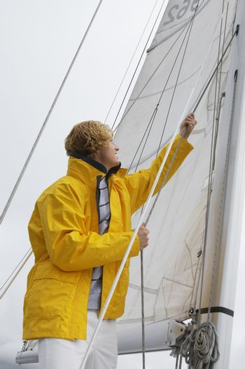 Young Caucasian man holding rigging on sailboat