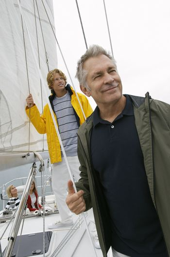 Happy Caucasian man with son on yacht during vacations