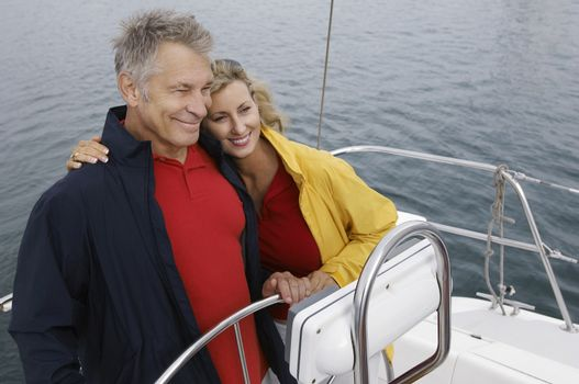 Happy Caucasian couple embracing on sail boat