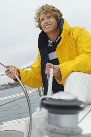 Caucasian young man holding rope of the winch and helm on sailboat