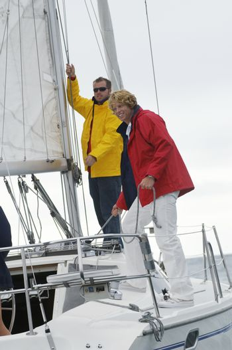Two happy Caucasian men sailing on sailboat