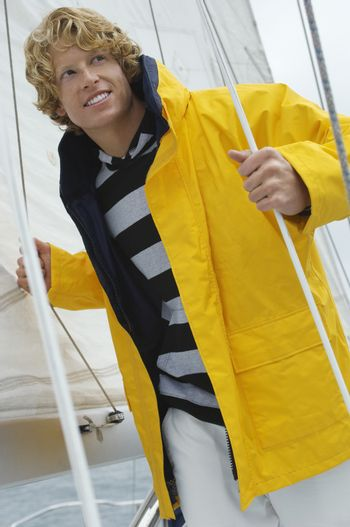 Young Caucasian man in yellow jacket standing on sailboat
