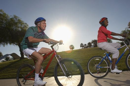 Senior couple cycling in park at dusk