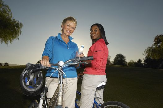 Senior women on bicycles at dusk portrait