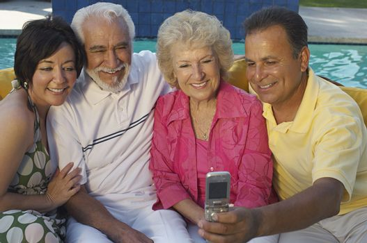 Happy family taking self portrait through cell phone