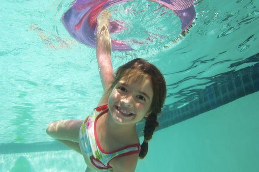 Portrait of a happy elementary girl swimming underwater with inflatable ring