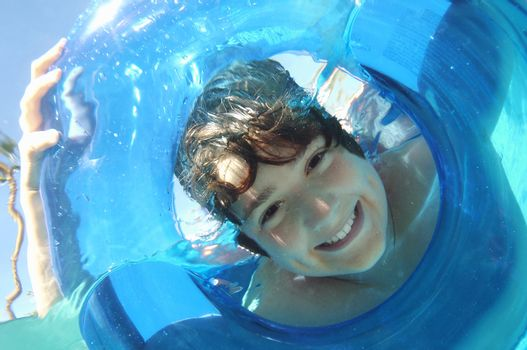 Portrait of a teenage boy looking through inflatable ring in water