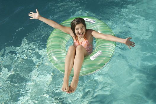 High angle view of little girl on inflatable ring with arms outstretched in swimming pool