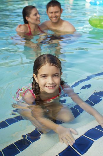 Portrait of a cute little girl in swimming pool with parents in the background
