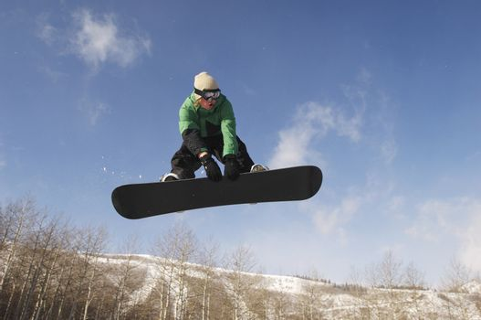 Low angle view of male snowboarder jumping against sky