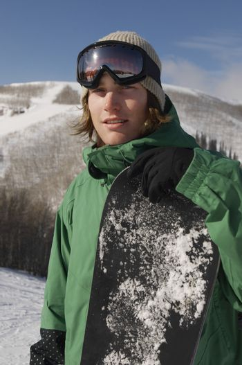 Portrait of young male snowboarder holding snowboard