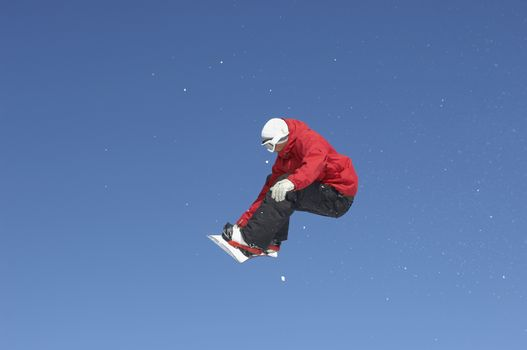 Full length of male snowboarder jumping against blue sky