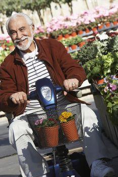 Portrait of a happy senior man on motor scooter at botanical garden
