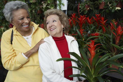 Two happy multiethnic senior female friends at botanical garden