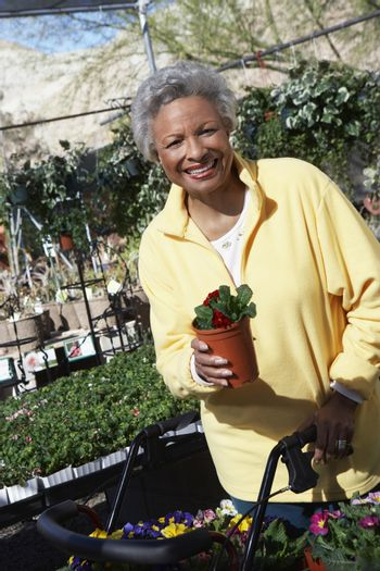 Portrait of an African American woman holding potted plant at botanical garden