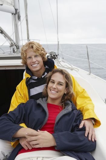 Portrait of a happy young couple embracing on sailboat during vacation