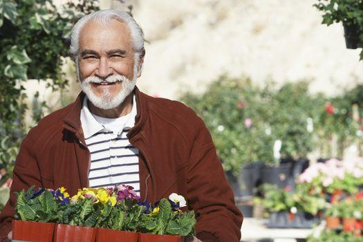Portrait of a happy senior man with flowerpots in botanical garden