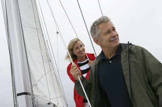 Happy Caucasian couple on sail boat looking away